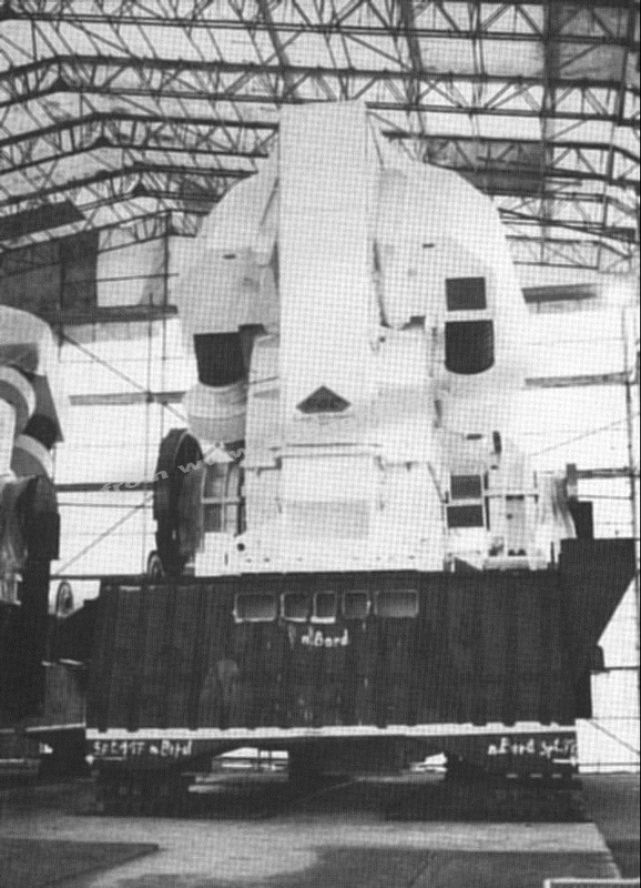 One of the giant GEC propulsion electric motors before installation and being lowered through the funnel hatch.  The funnel can be seen on the quayside off to the left. The ships mast is to the right.