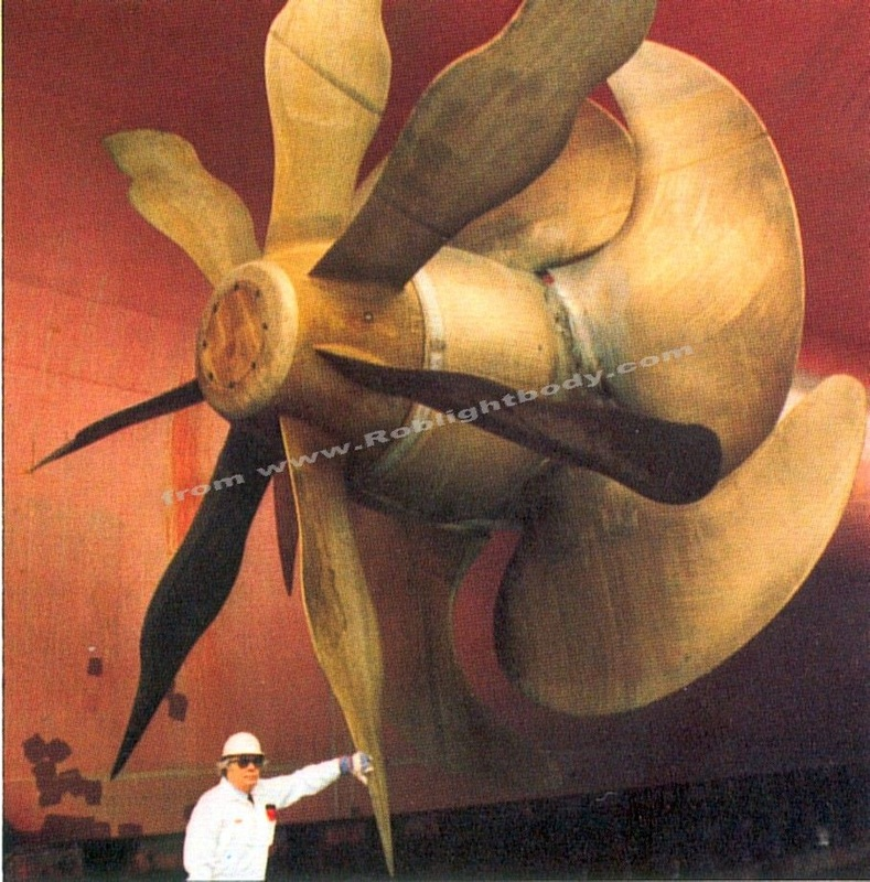 A QE2 propeller with a man underneath to show scale