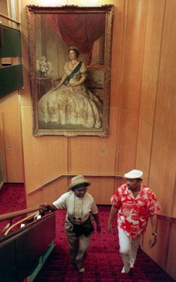 ROYAL VISAGE: Wilhelmina and George Glanville of New York walk up a stairwell on the QE2 with a portrait of Queen Elizabeth behind them.